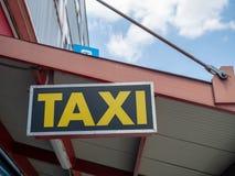 Gult taxitecken som hänger ovanför utomhus- väntande område arkivfoton