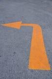 Gult tecken för vänstersida på den konkreta vägen. Arkivbilder