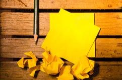 Gult tomt papper med den skrynkliga papper och blyertspennan på wood pettern Arkivbild
