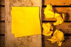 Gult tomt papper med skrynkligt papper på en gammal bok på wood pettern Royaltyfria Foton