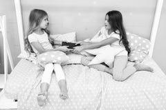 Gulzig jonge geitjesconcept De kwesties van zustersrelaties Aandeelboek met vriend De kinderen in slaapkamer willen gelezen het g stock afbeeldingen
