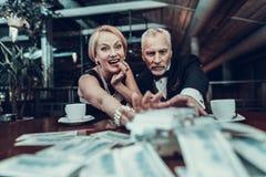 Gulzig Vrouw en Man bereik voor stapel van geld stock afbeeldingen