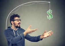 Gulzige mens die dollarrekening op grijze achtergrond achtervolgen Stock Fotografie