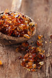 Gum arabic, also known as acacia gum - in  old wooden spoon Royalty Free Stock Image