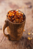 Gum arabic, also known as acacia gum - in wooden mug. Gum arabic, also known as acacia gum - in wooden antique mug royalty free stock photography