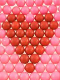 Gumball Heart. Red heart made of gumballs surrounded by pink gumballs Stock Photo