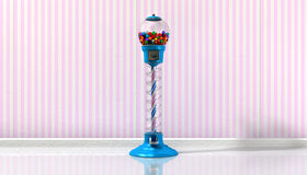 Gumball Machine In A Candy Store. A regular blue vintage gumball dispenser machine made of glass and reflective plastic with chrome trim filled with multicolored royalty free stock images