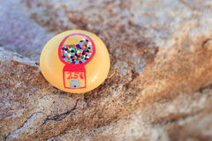 Gumball machine picture painted on small yellow rock. Small yellow painted rock has a picture of a red gumball machine with a 25 cent price. Rock is for yard or stock image