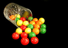 Gumballs and glass. Colorful gumballs spilling from a glass on a black background stock photo