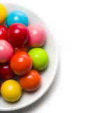 Gumballs on a Plate. Multicolored gumballs sitting in a white plate on a white background stock photography