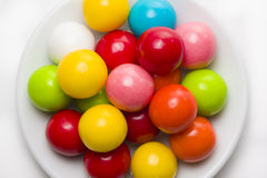 Gumballs on a Plate. Multicolored gumballs sitting in a white plate on a white background stock image