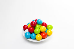 Gumballs on a Plate. Multicolored gumballs sitting in a white plate on a white background stock images