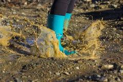 Gumboots бирюзы брызгая в лужице Стоковое Изображение