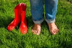 Gumboots сада босоногой девушки стоя следующие красные на траве Стоковая Фотография RF