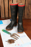 Time to work. Time to get your hands dirty. Gumboots, garden fork and soil on a calender against a rough wooden background royalty free stock photo
