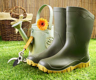Gumboots and gardening tools. Pair of green rubber gumboots, pruning shears and a metal watering can on a neatly trimmed green lawn with a wicker basket in the Stock Photo