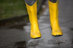 Gumboots are jumping into a water puddle Royalty Free Stock Photos
