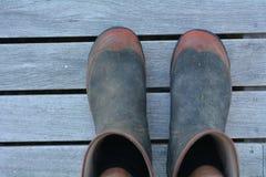 Gumboots Mans садовничая на деревянных панелях стоковая фотография rf