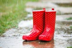 Gumboots rossi in pioggia Fotografia Stock