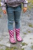 Gumboots splashing through a rain puddle Stock Photography