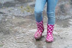 Gumboots splashing through a rain puddle Royalty Free Stock Image