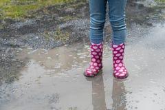 Gumboots splashing through a rain puddle Stock Photos