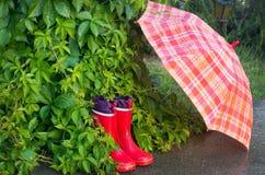 Gumboots and umbrella. Wet gumboots and umbrella in garden Stock Photos