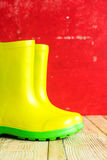Gumboots on wooden old background. Wall Stock Images