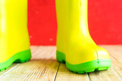 Gumboots on wooden old background. Wall Stock Image