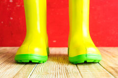 Gumboots on wooden old background. Wall Stock Photos