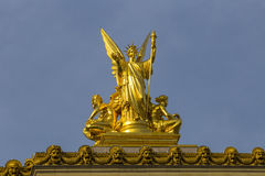 Gumery Poetry. Golden sculpture of Gumery Poetry ornamenting the facade of the Garnier Opera of Paris on blue stock images