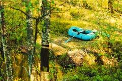 Gummiboot auf dem Ufer Stockfotografie