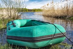 Gummiboot liegt am Wasser im hintergrund der Teich. Fishing inflatable rubber boat standing on the shore of lake. Dinghy with oars Royalty Free Stock Photography