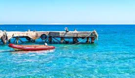 Gummiboot nahe dem Pier im Meer lizenzfreie stockbilder