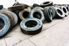 Gummihjul överhopar på cementden jordnear väggen, gummihjul för använd bil Royaltyfri Foto
