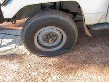 Gummihjul för skada för bilhjul plant på medlet royaltyfria foton