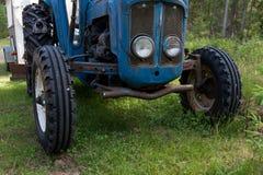 Gummihjul på blåa gras för ett traktoranseende I royaltyfri fotografi