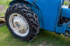 Gummihjul på blåa gras för ett traktoranseende I arkivbilder
