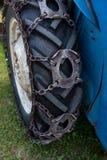Gummihjul på blåa gras för ett traktoranseende I royaltyfri bild