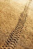 Gummihjulspår i sand Arkivfoto