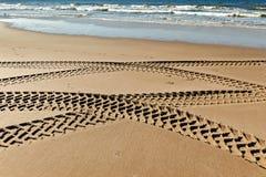 Gummihjulspår på en strand Arkivfoto