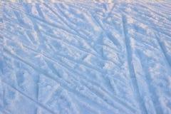 Gummihjulspår på ren vit snö på en solig och frostig vinterdag Kaotisk rörelse royaltyfria foton