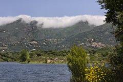 Gummilacka de Padula (Padula sjön), i bakgrunden bergbyn Oletta i den Nebbio regionen, nordliga Korsika Royaltyfria Foton