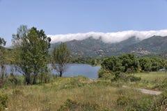 Gummilacka de Padula (Padula sjön), i bakgrunden bergbyn Oletta i den Nebbio regionen, nordliga Korsika, Frankrike arkivbild
