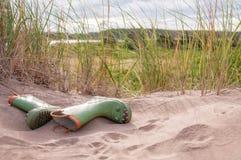 Gummiregen-Stiefel auf dem Strand Stockbilder