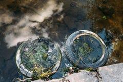 Gummireifen dreht sich nahe Ufer des Wasserreservoirs, Verschmutzung von Umwelt und Meer Lizenzfreie Stockbilder