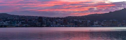 Gummistövel Nya Zeeland, färgrik solnedgång för panorama över lugna hamn arkivbilder