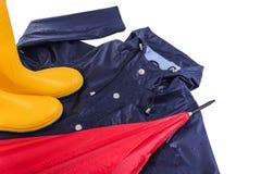 Gummistöveler och regnrock och paraply i regndroppar Arkivbilder