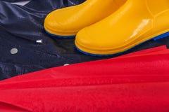 Gummistöveler och regnrock och paraply i regndroppar Royaltyfri Bild