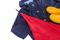 Gummistöveler och regnrock och paraply i regndroppar Arkivfoto